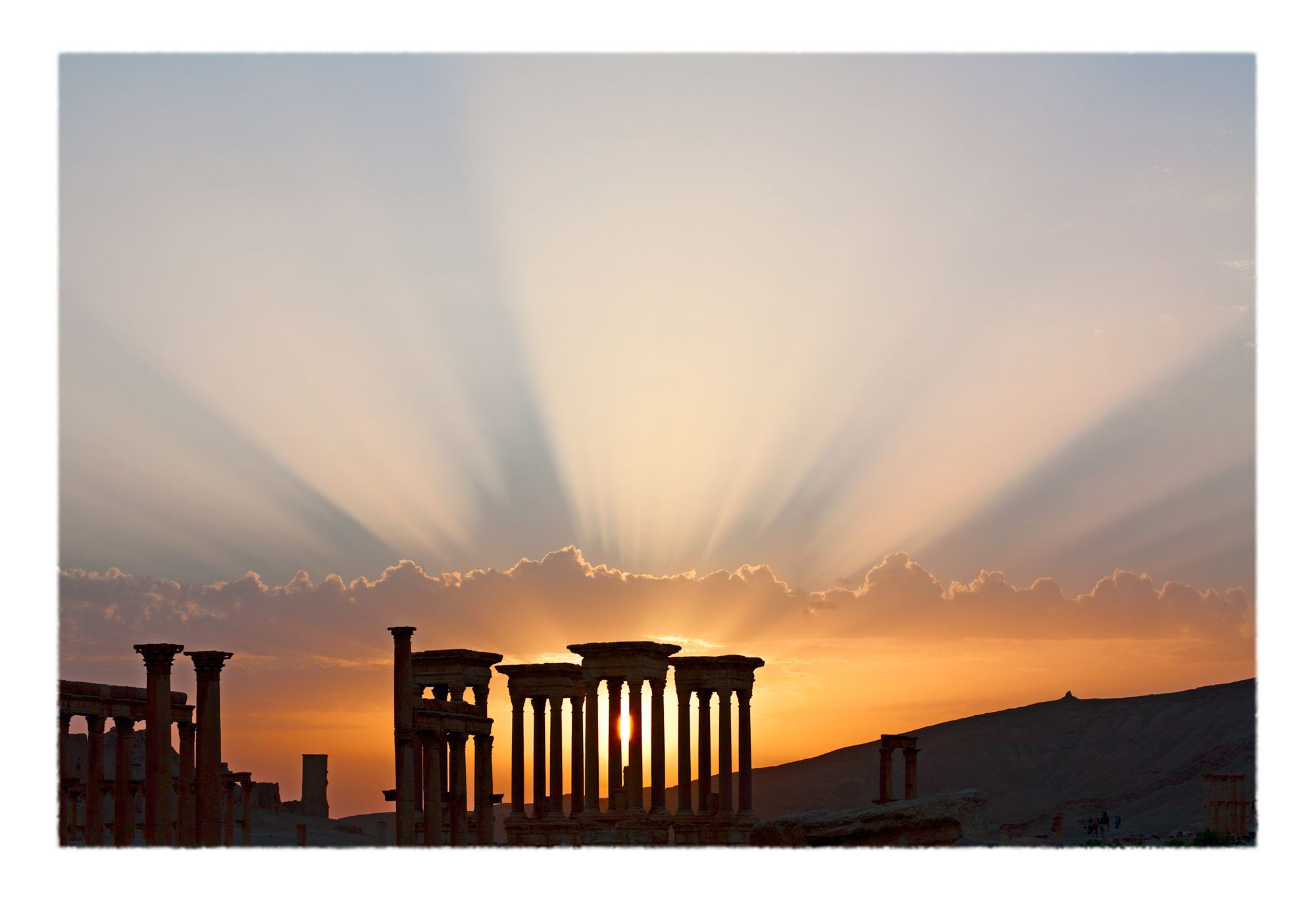 Radial spokes of sunset light over the Roman-era archaeological ruins of Palmyra, Syria