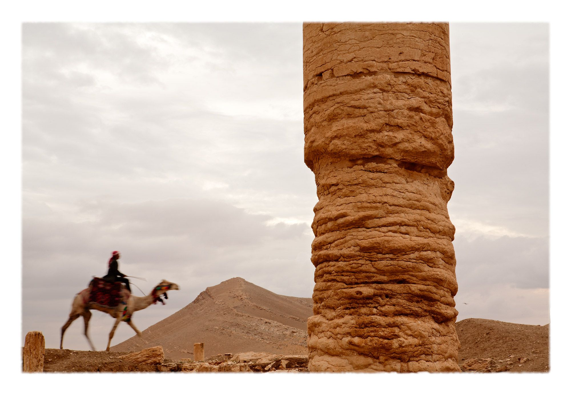 Dessicated windblown sandblasted and expressively eroded column behind which a man rides a colorfully bedecked camel. The tones and textures of erosion on once glorious specimens of  artisanal production are eloquent testaments to the relative nature of evanescence.