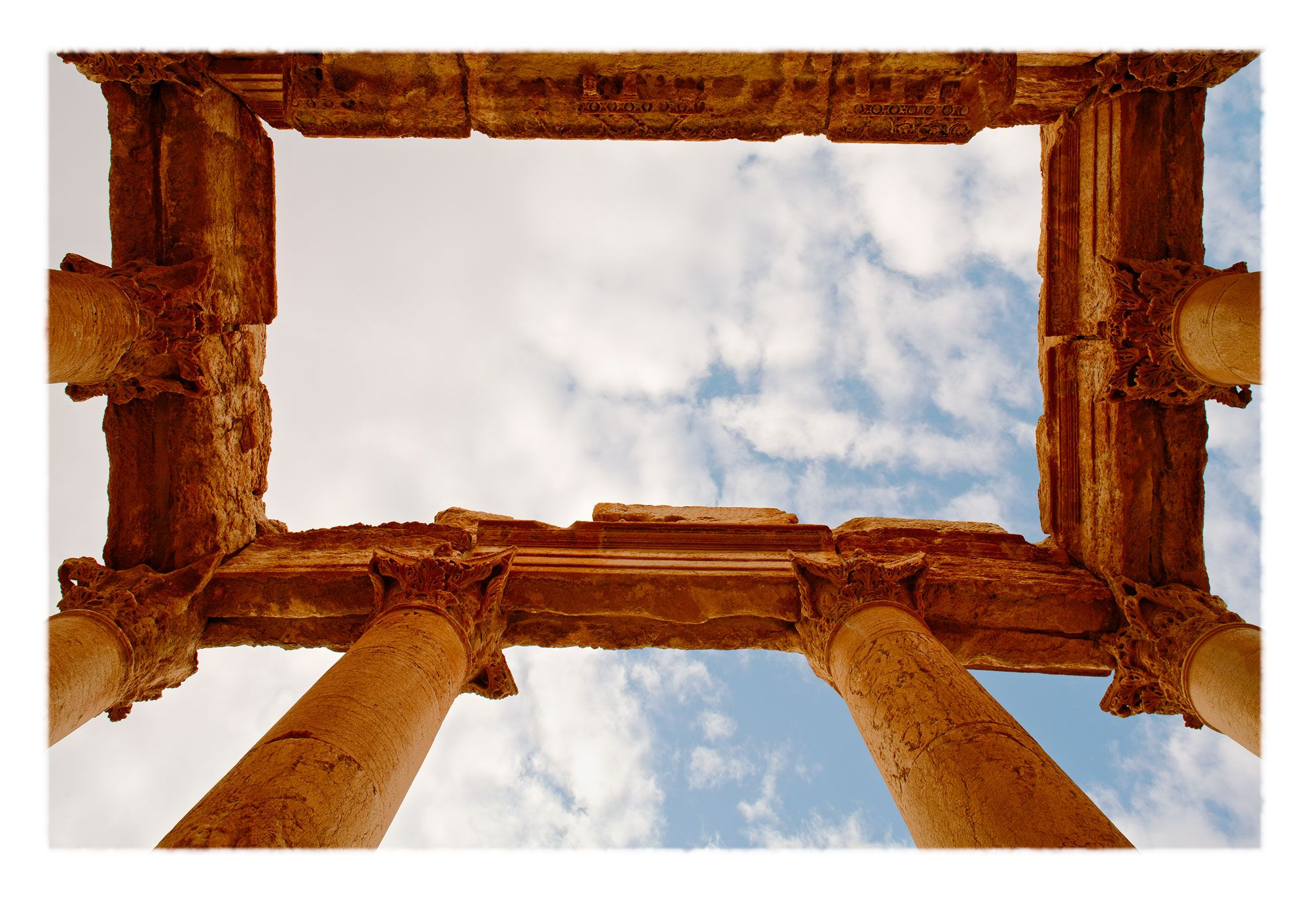View upwards through Corinthian capitals of furled acanthus leaves with eroded entablature, sky and clouds. Destroyed Palmyra, Syria.